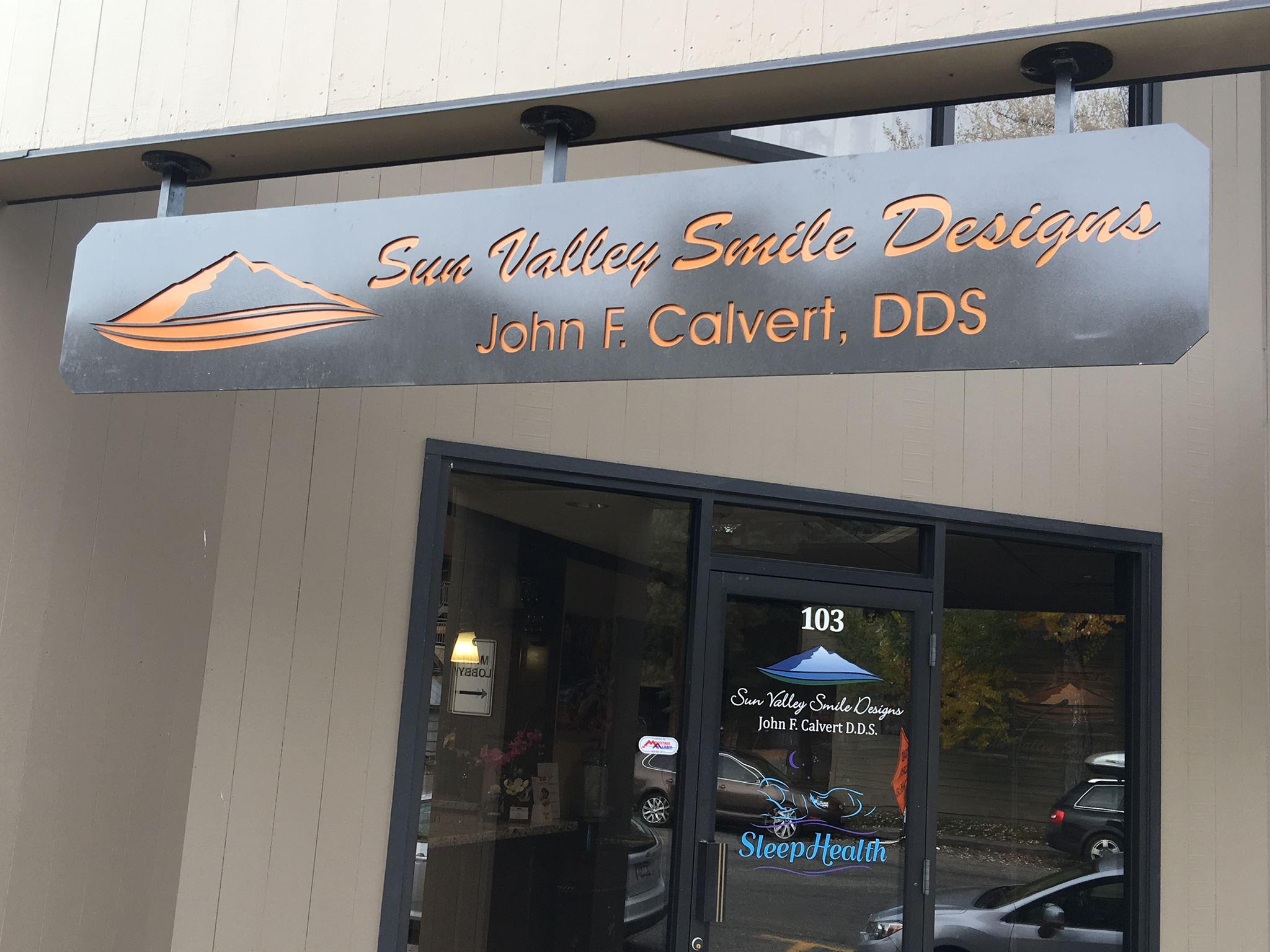 "The exterior front of a building. There is a glass entry door with a large window attached to each side of the door. There is an over head sign that reads ""Sun Valley Smile Designs John F. Calvert, DDS"""